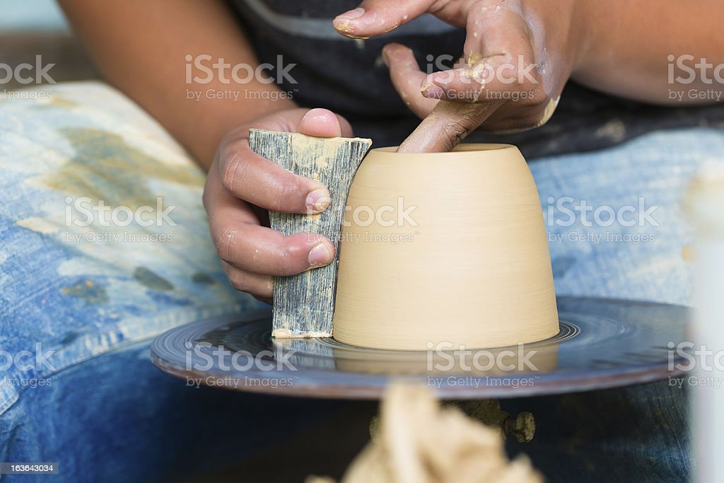Potter creating clay bowl on turning wheel royalty-free stock photo