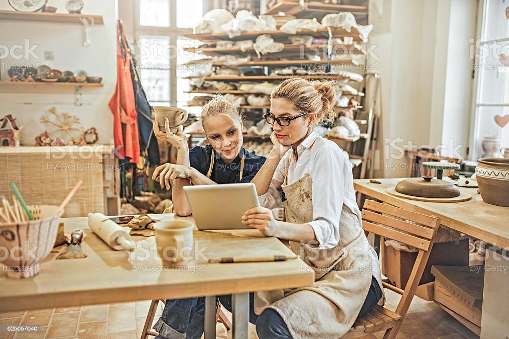 Potter entrepreneur using digital tablet  in workshop stock photo