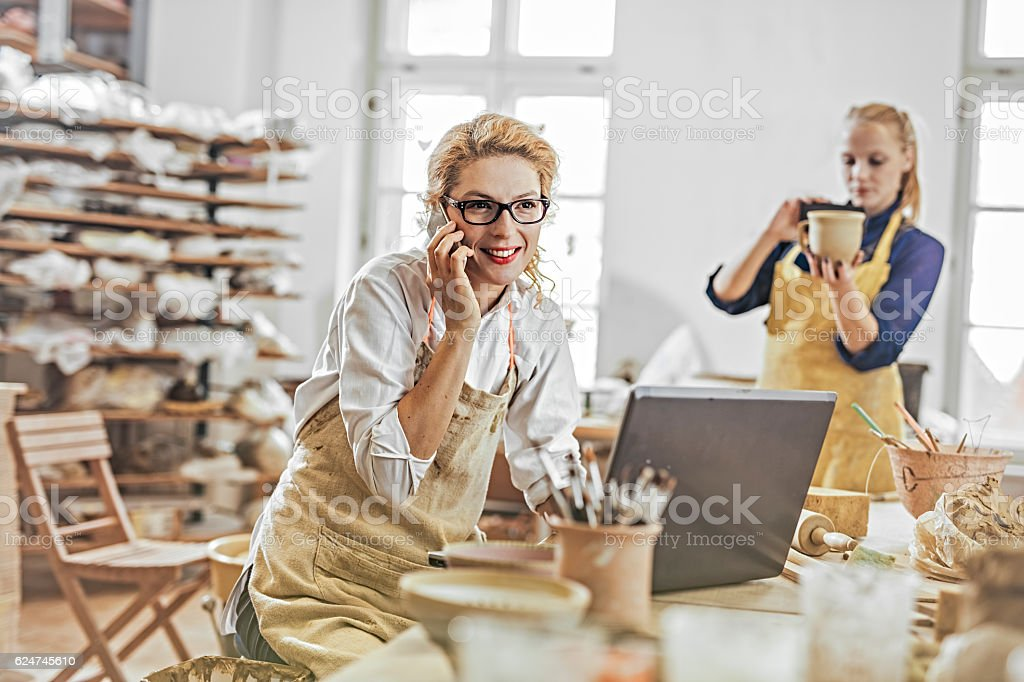 Potter entrepreneur using laptop and mobile phone  in workshop stock photo