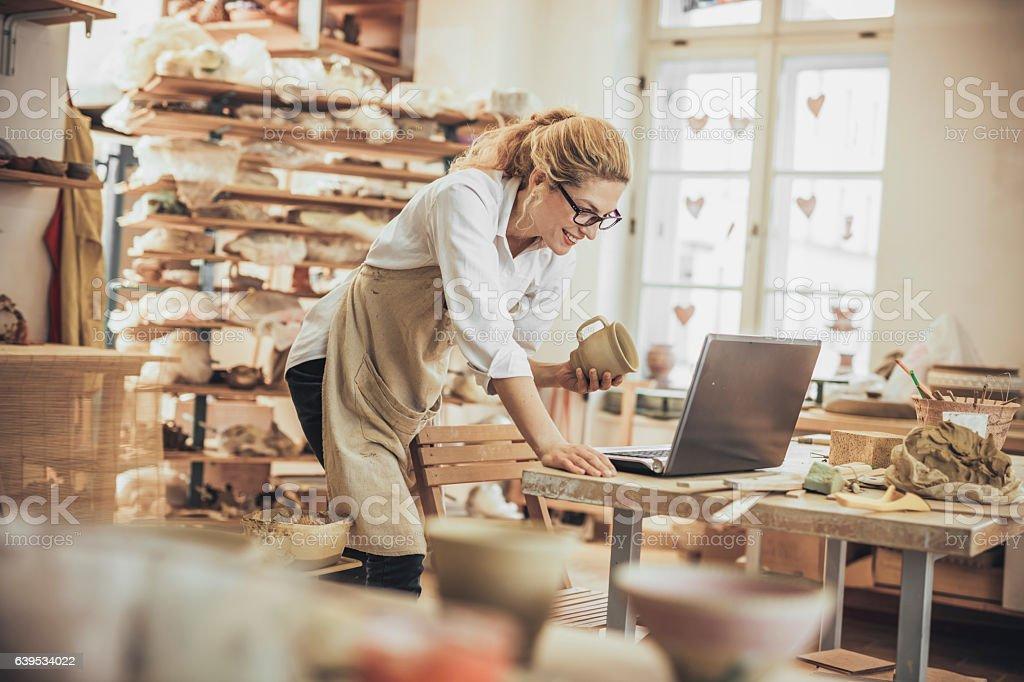 Potter entrepreneur using laptop  in workshop stock photo
