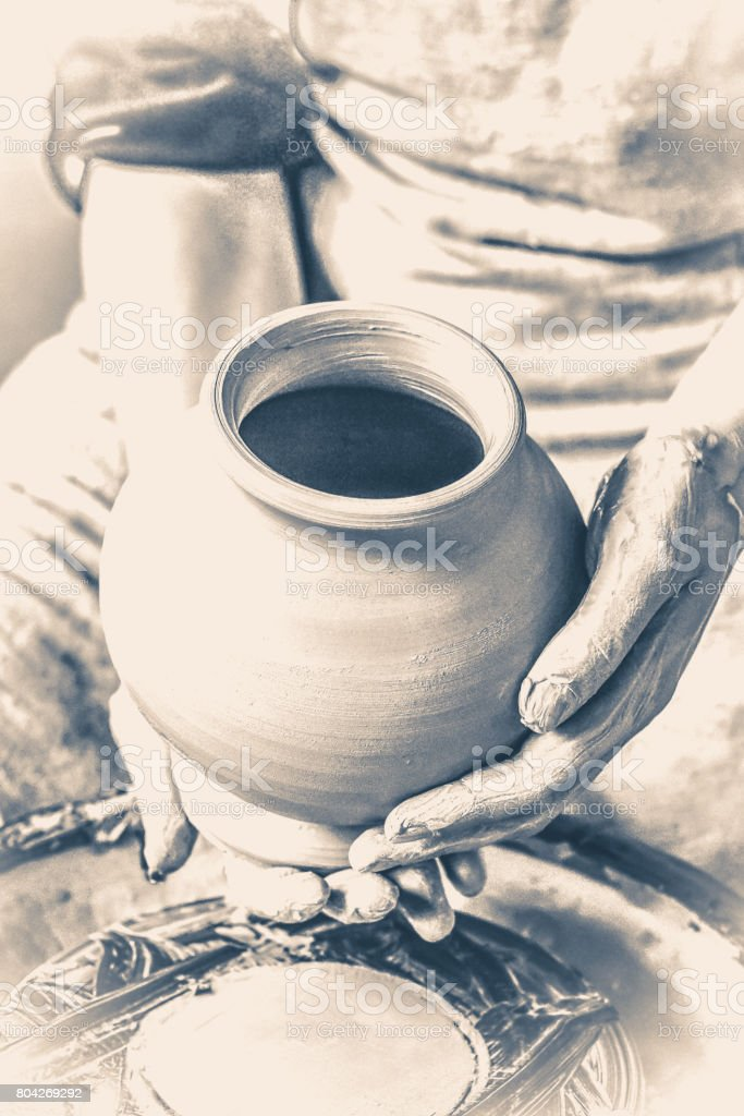 Potter holds more crude to the firing of white clay jug. Old vintage style. stock photo