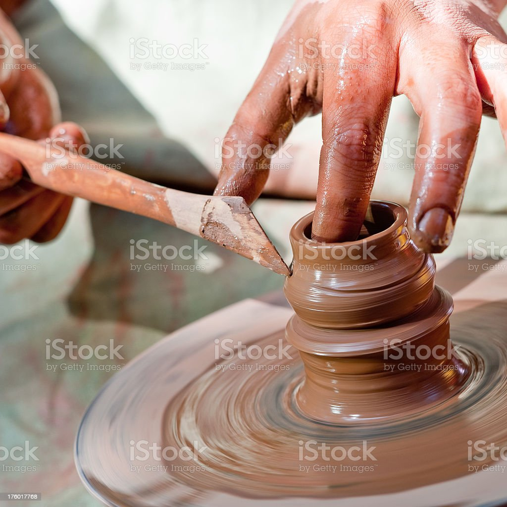 potter inflicts a decorative pattern on spinning pot royalty-free stock photo