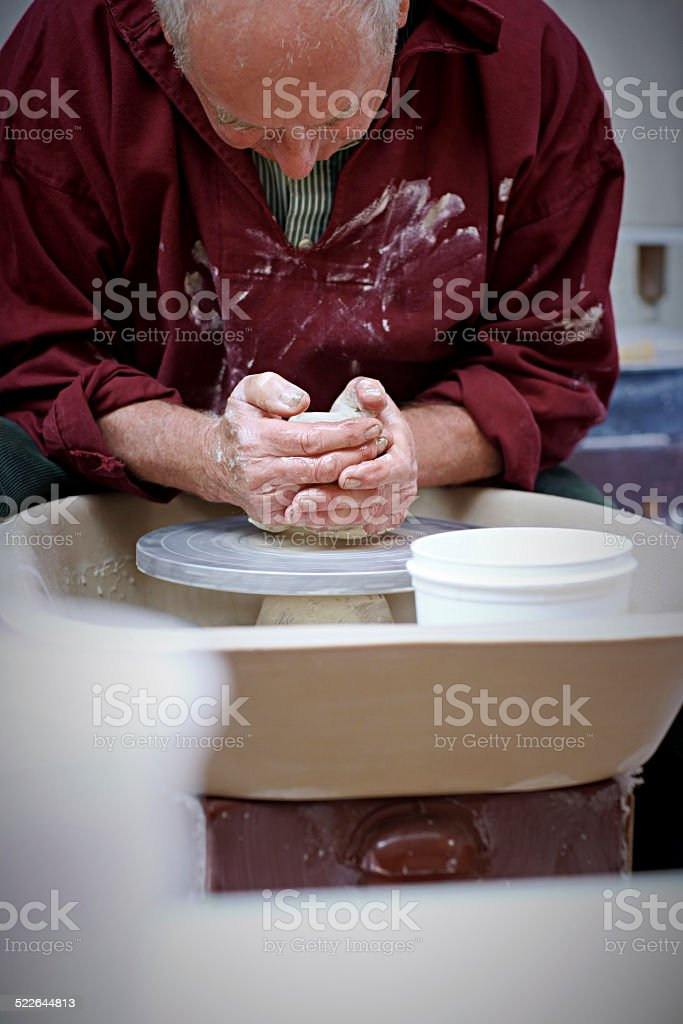 Potter placing clay on pottery wheel stock photo