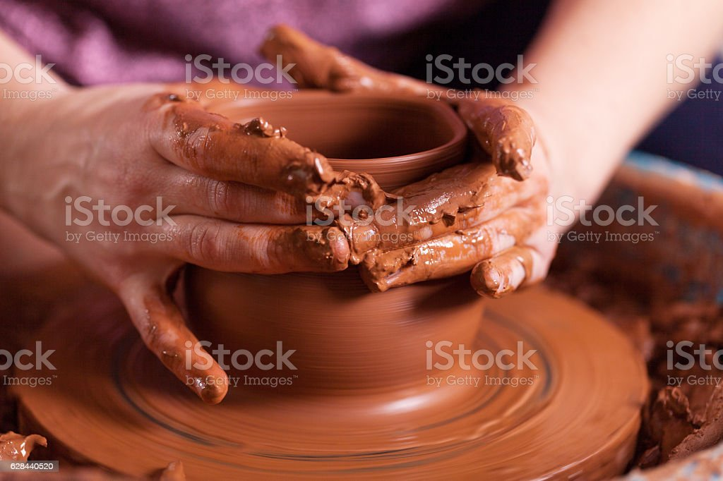 Potter shaping clay on the pottery wheel stock photo
