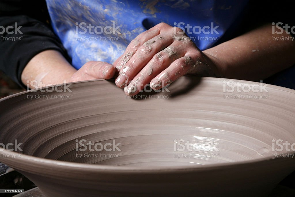 Potters hands shaping rim of clay bowl stock photo