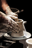Potters Hands turning a beaker on potter wheel.