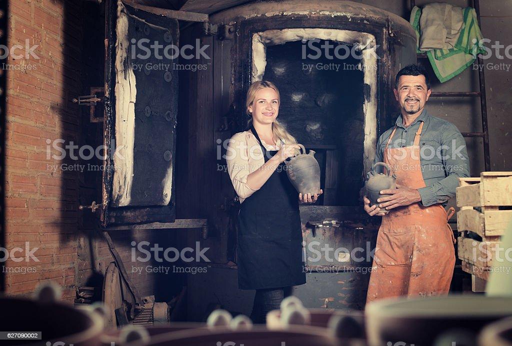 potters holding black ceramic vases stock photo