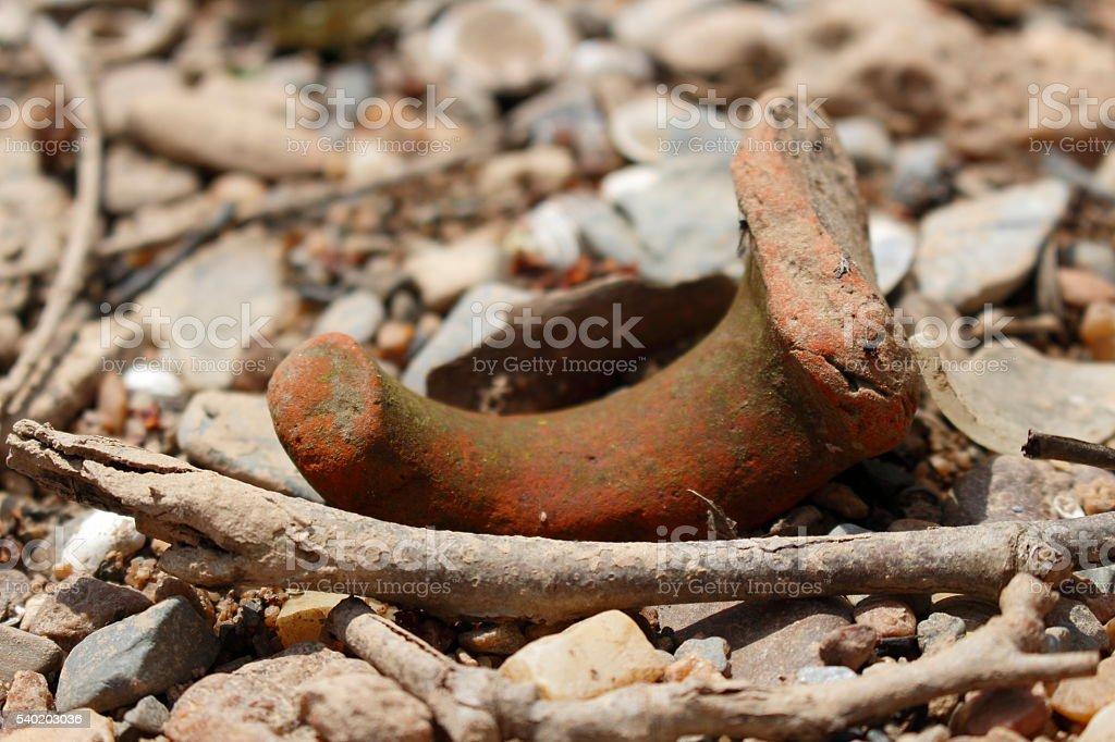 Pottery shard on river bank stock photo