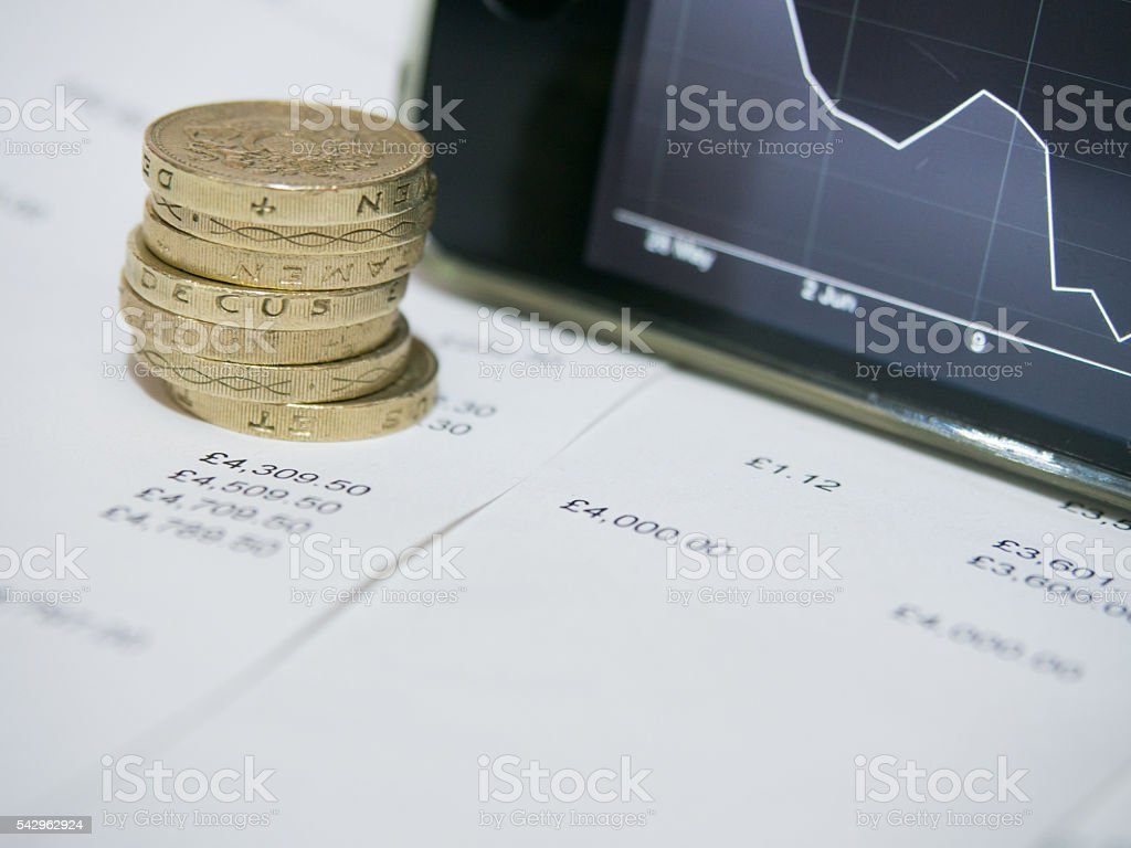 Pound coins on financial figures sheet with a decreasing graph. stock photo