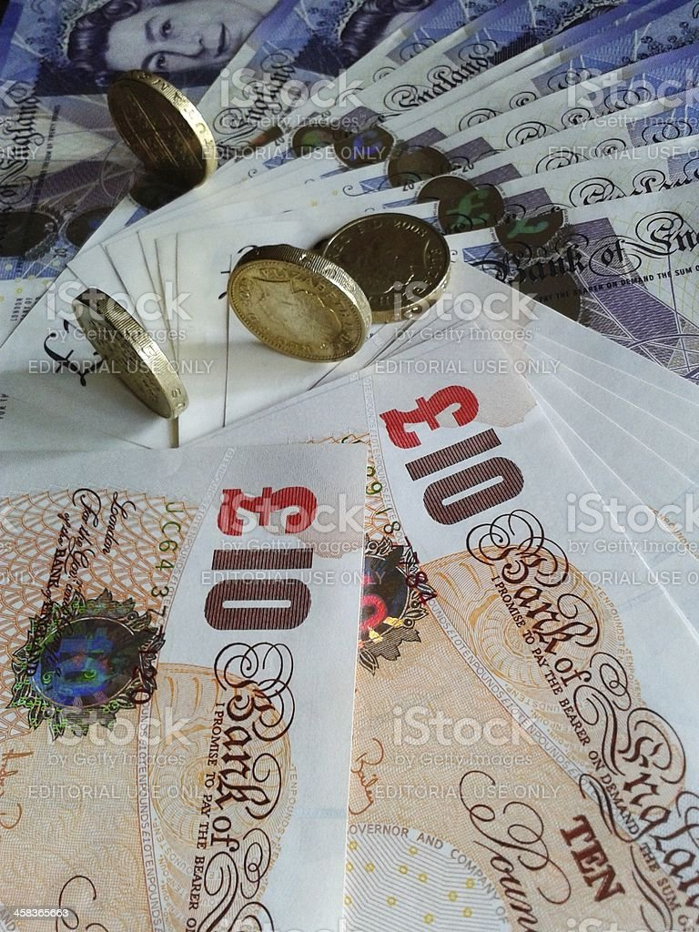 Pound coins on the edge at new banknotes royalty-free stock photo
