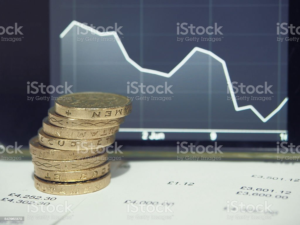 Pound coins with graph of decreasing graph. stock photo