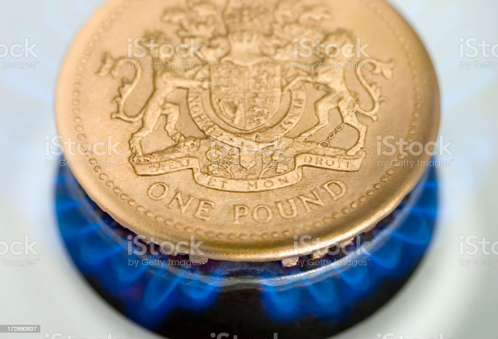Poung coin on top of a gas flame showing the cost of gas stock photo