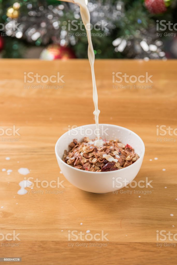 Pour the milk into the bowl of cereal. stock photo