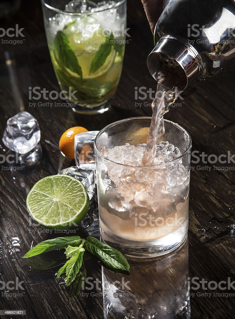 Pouring a cocktail into glass stock photo