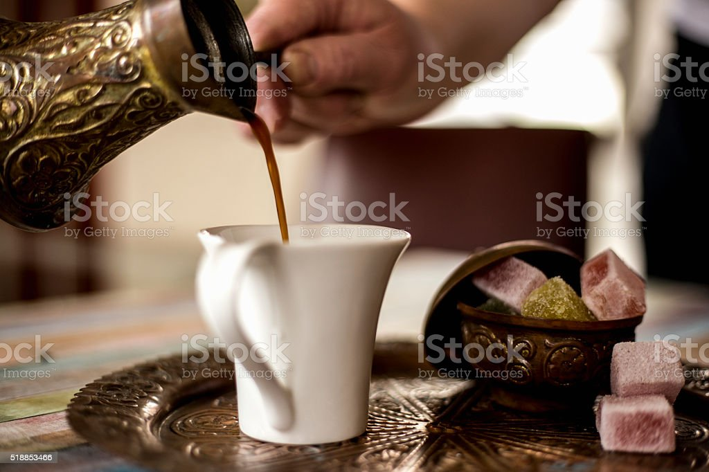 Pouring a cup of thick Turkish coffee stock photo