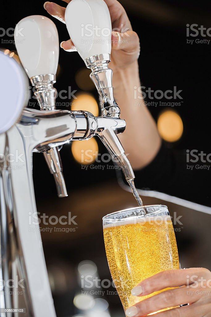 Pouring a Draft Blonde Beer from the Tap stock photo