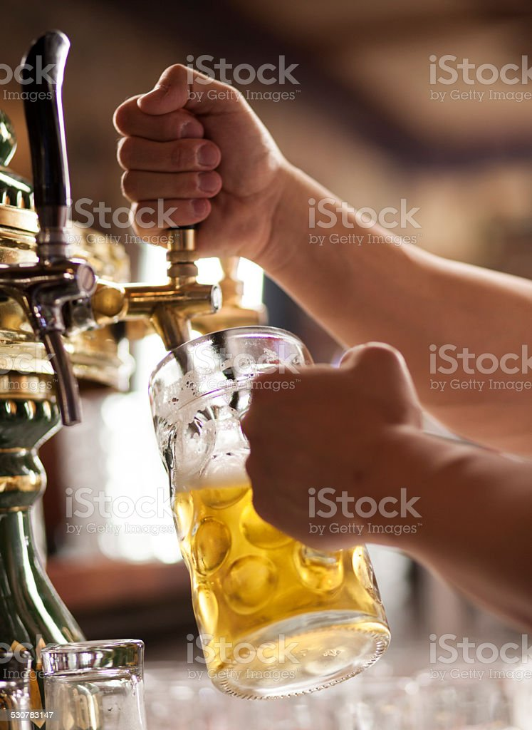 Pouring a glass of beer. stock photo