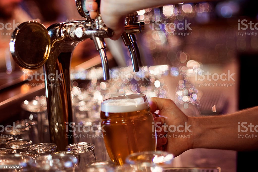 Pouring a glass of beer stock photo