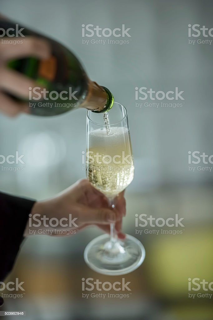 Pouring a glass of champagne stock photo