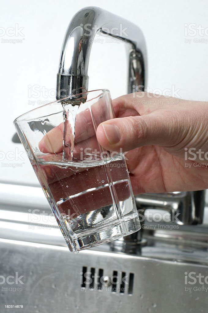 Pouring a glass of water from a faucet royalty-free stock photo