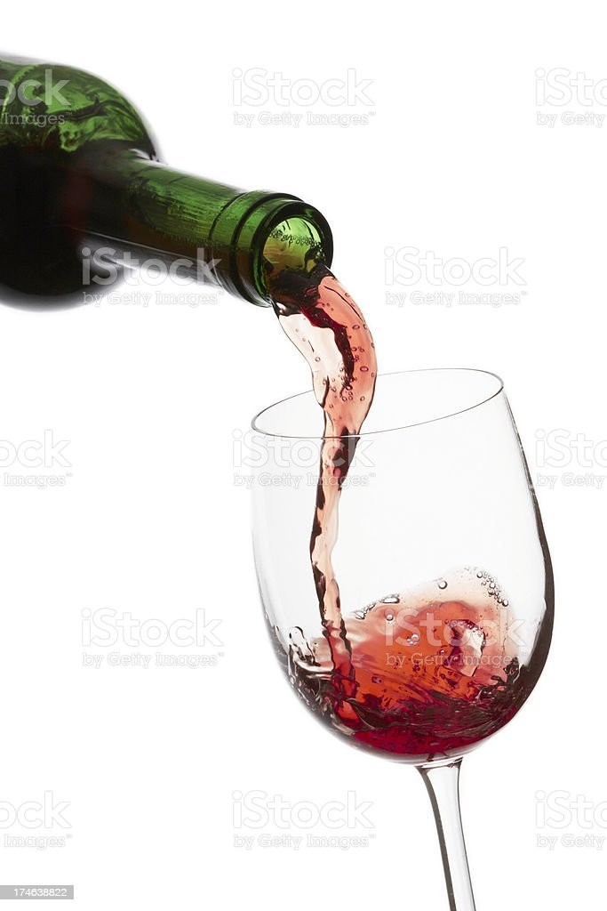 Pouring a glass of wine on white background stock photo