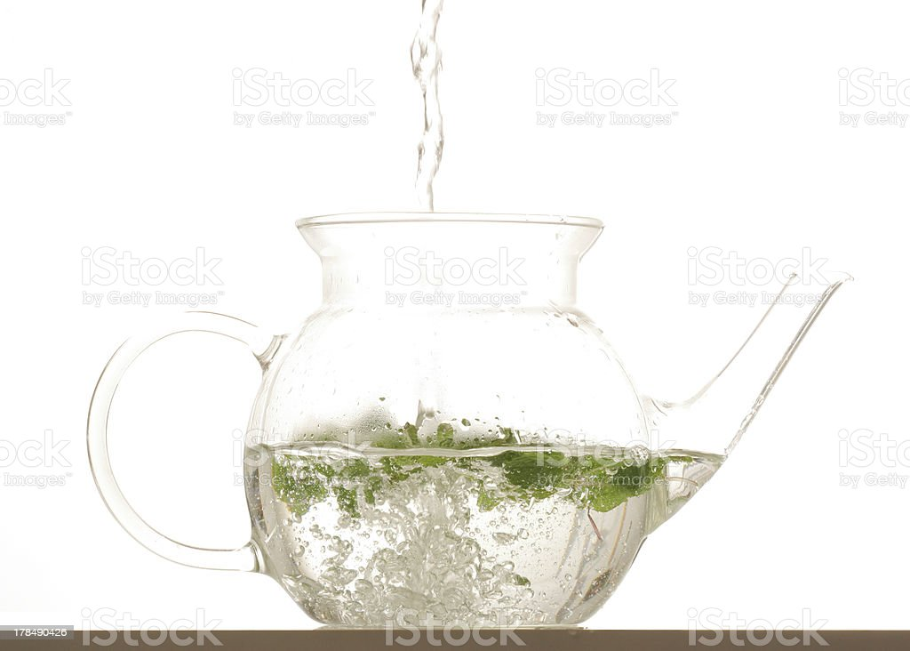 Pouring a glass pot of herbal tea stock photo