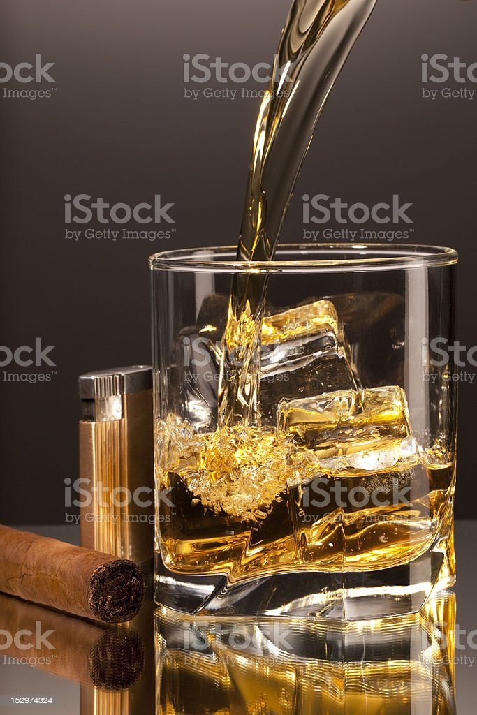 Pouring alcohol into a glass, Cigar and Lighter beside. royalty-free stock photo