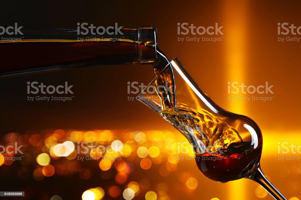 Pouring alcohol into a glass stock photo