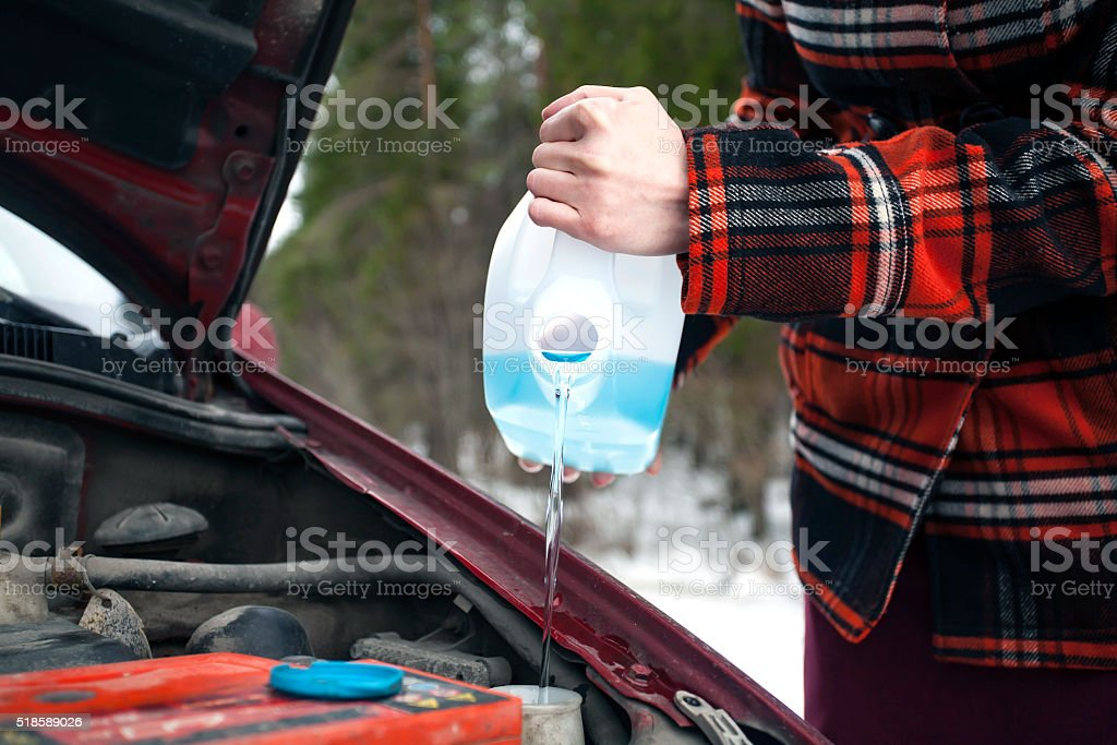 Pouring Antifreeze Washer Fluid into Windshield Washer Tank stock photo