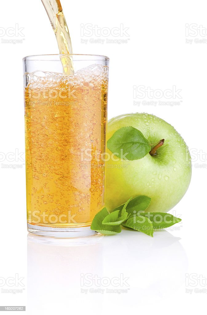 Pouring apple juice into glass, green juicy apples with leaf royalty-free stock photo