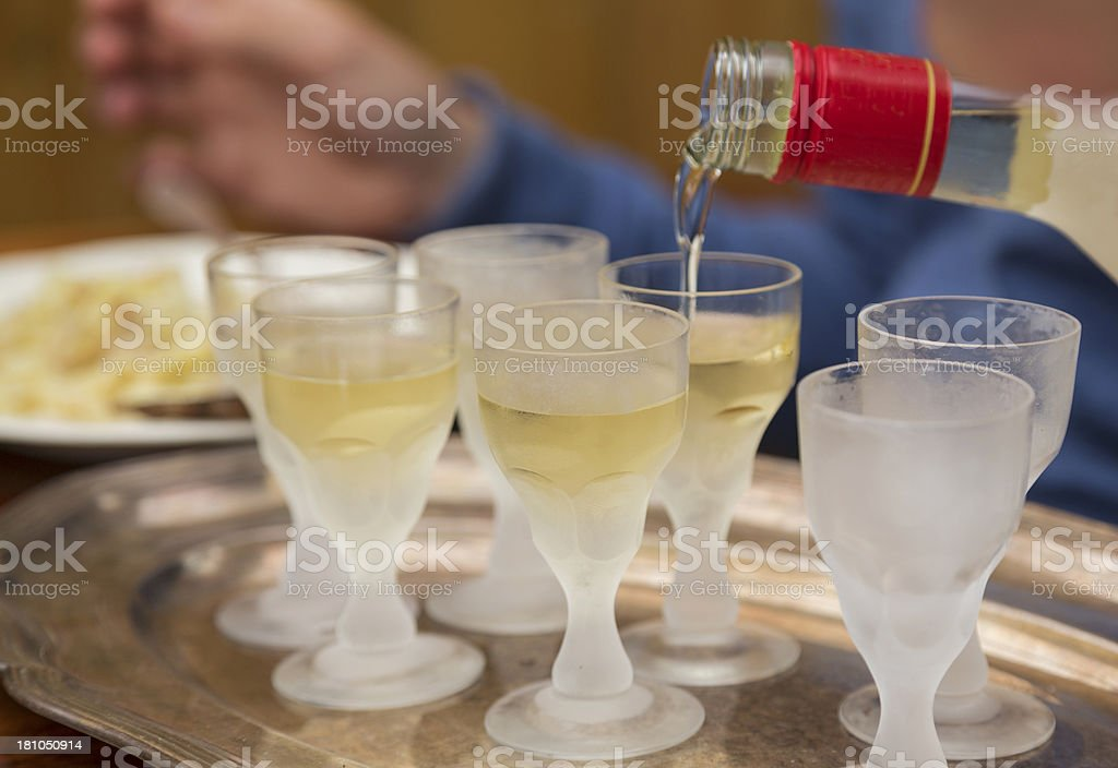 Pouring Aquavit into frosted glasses. stock photo
