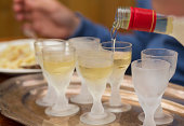 Pouring Aquavit into frosted glasses.