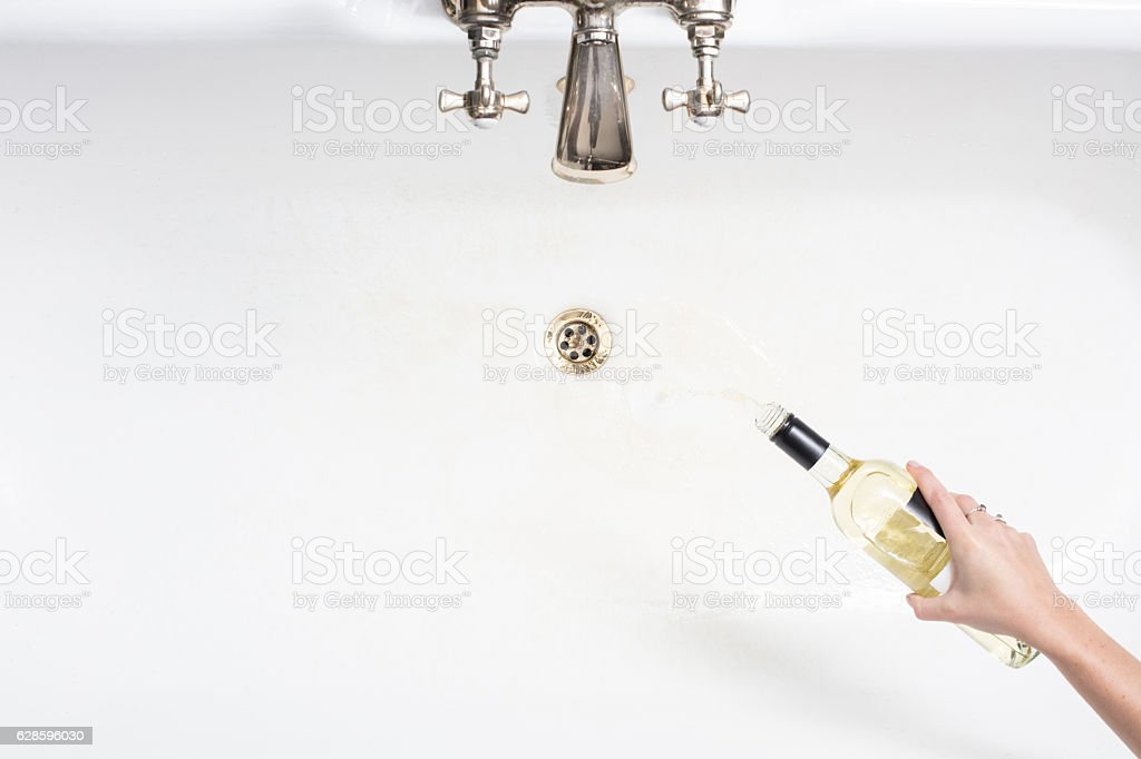 Pouring away wine in an act of giving up alcohol stock photo