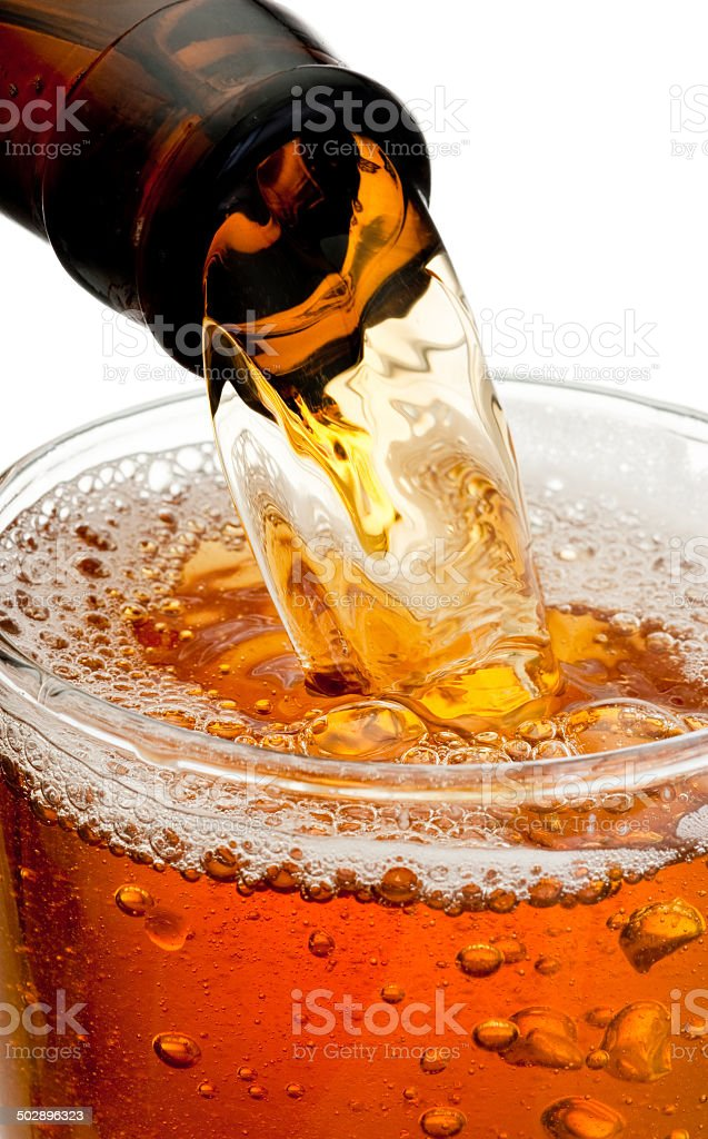 Pouring beer from bottle isolated on white background stock photo