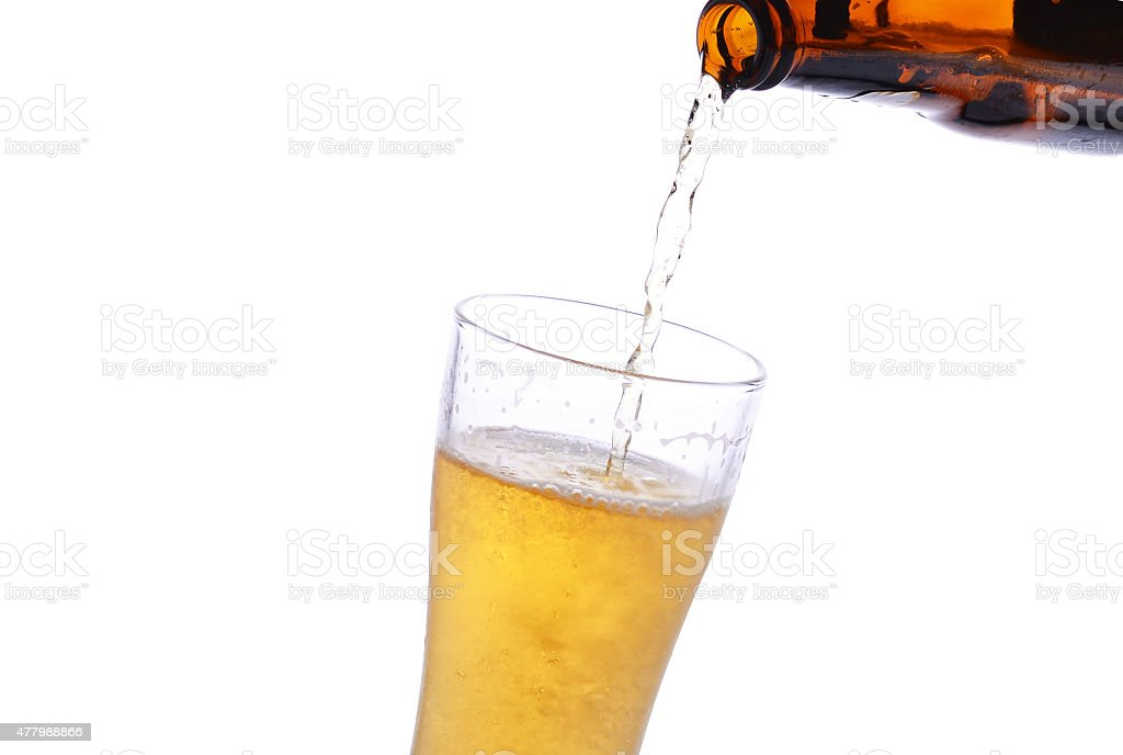 Pouring beer from bottle to stein stock photo