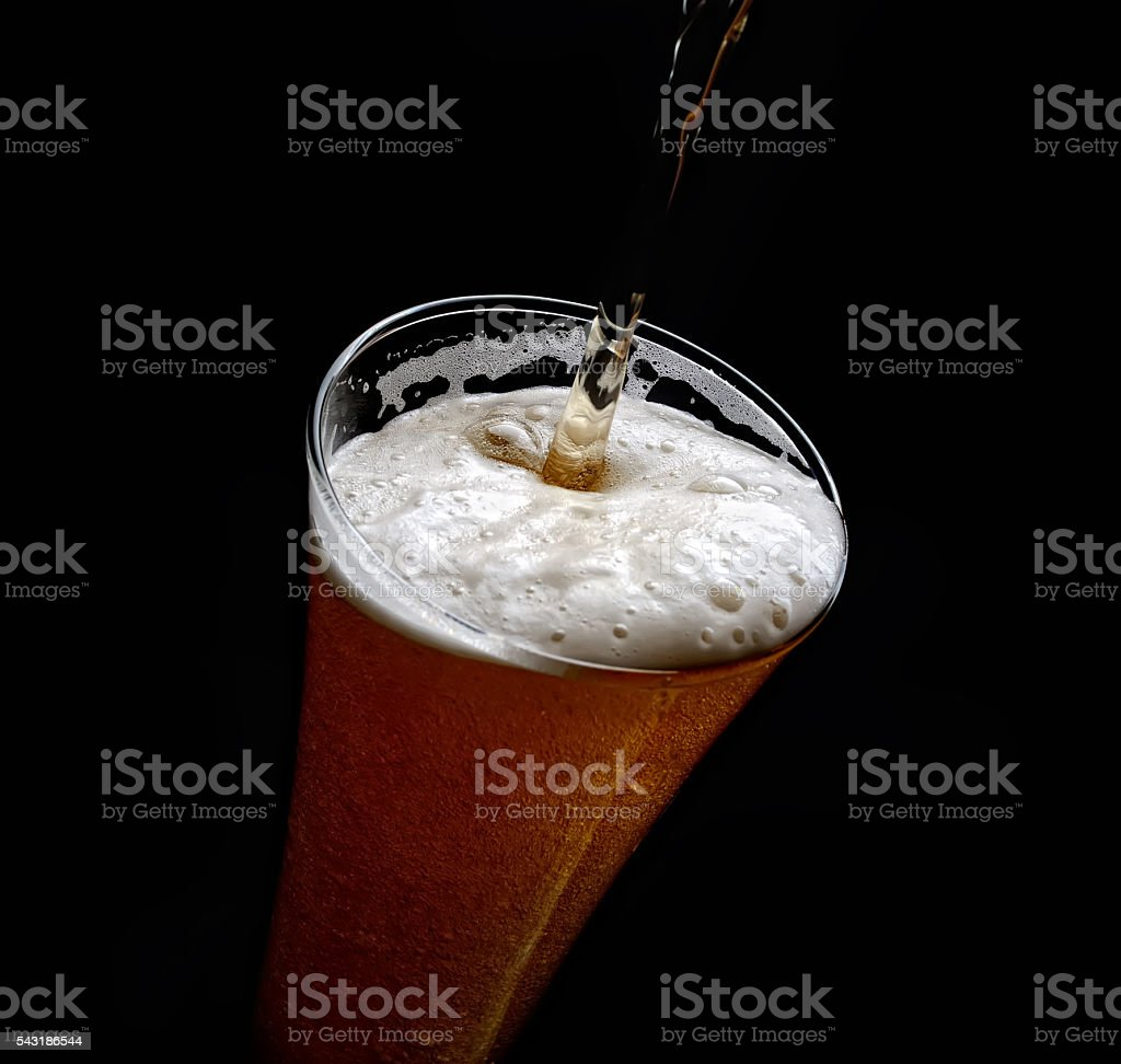 pouring beer in a glass on a black background stock photo