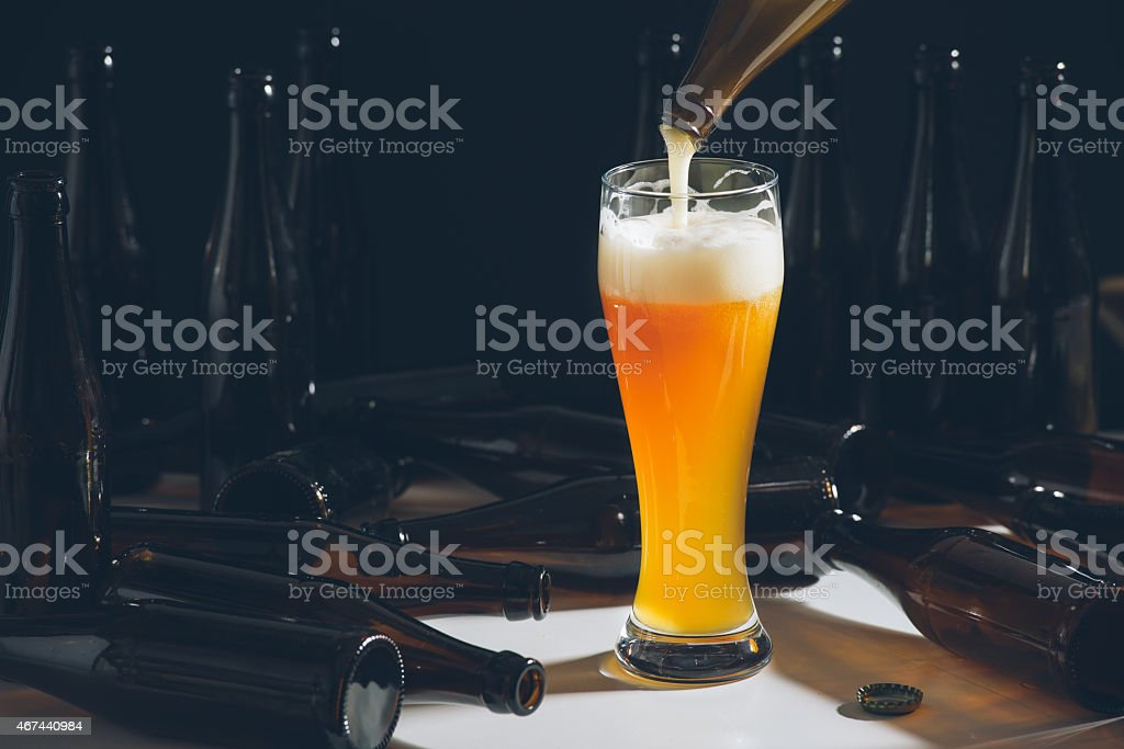 pouring beer in a glass stock photo