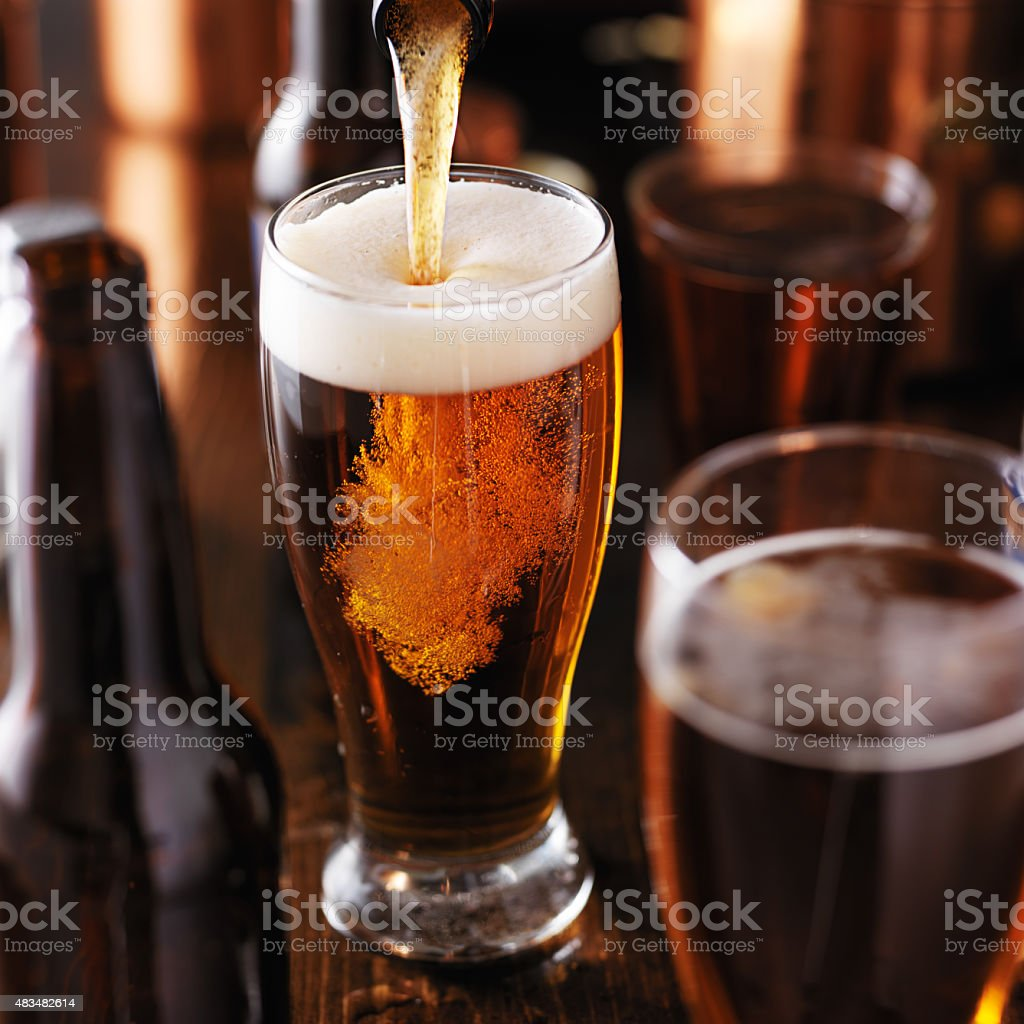 pouring beer into glass on wooden table stock photo