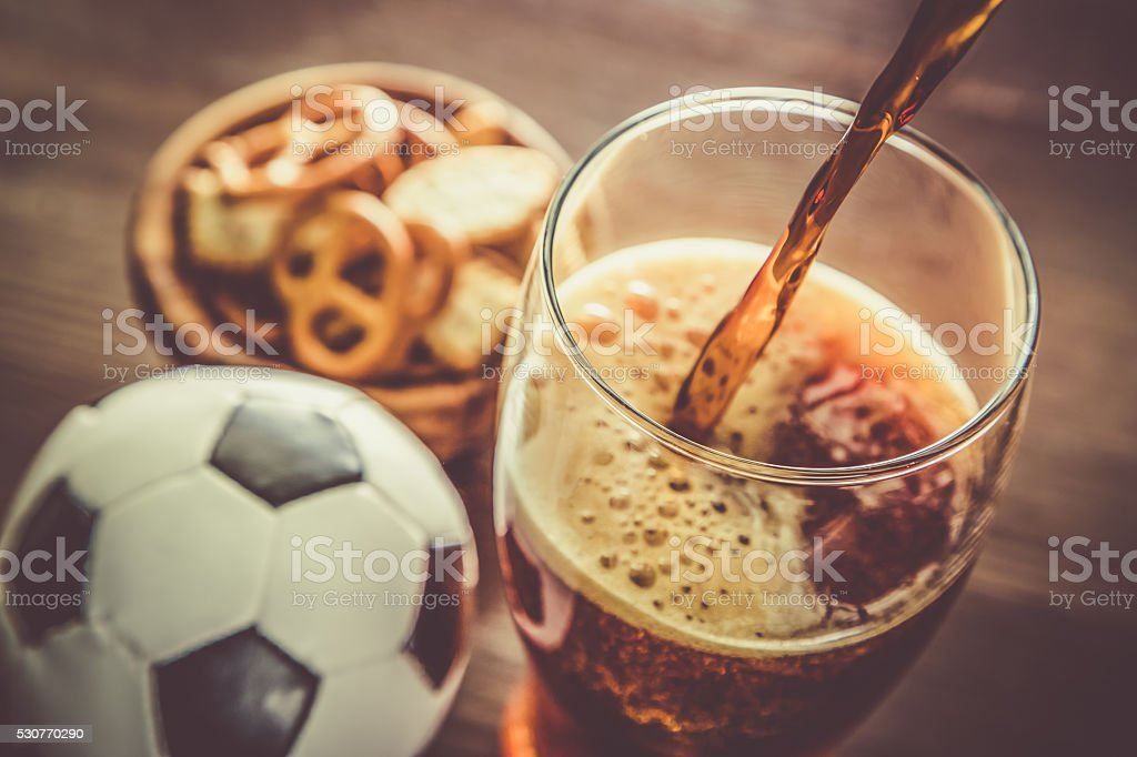 Pouring beer into glass with snacks and football stock photo