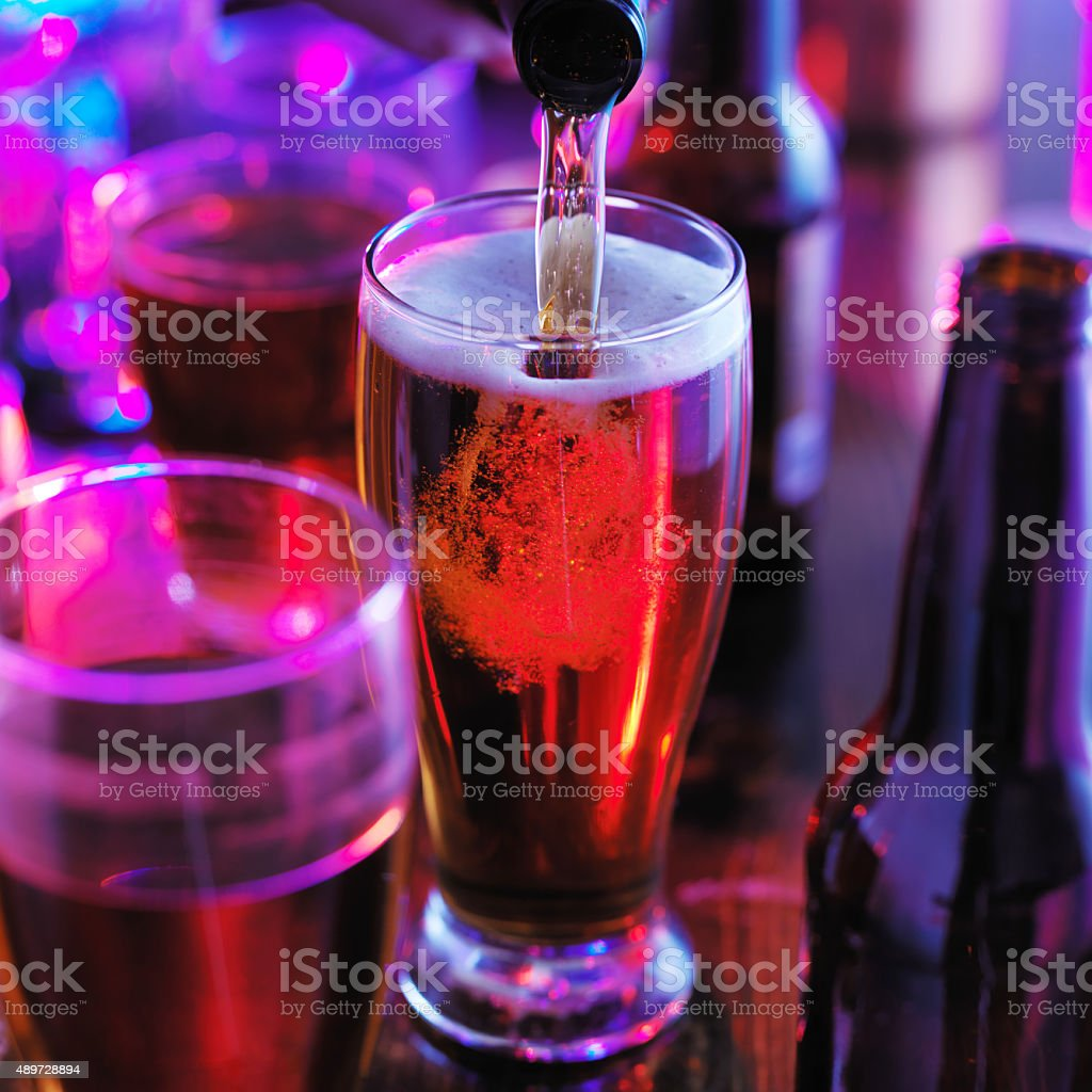 pouring beer into pint glass with colorful lights stock photo