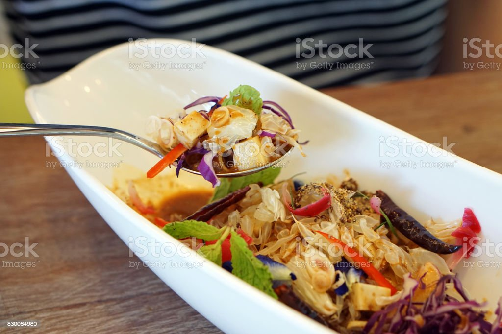 Pouring budu dressing on spicy rice salad with variety of vegetable (carrot, winged bean, cucumber, gotu kola, beetroot, torch ginger, butterfly pea, lemon grass, macadamia, flaxseed). stock photo