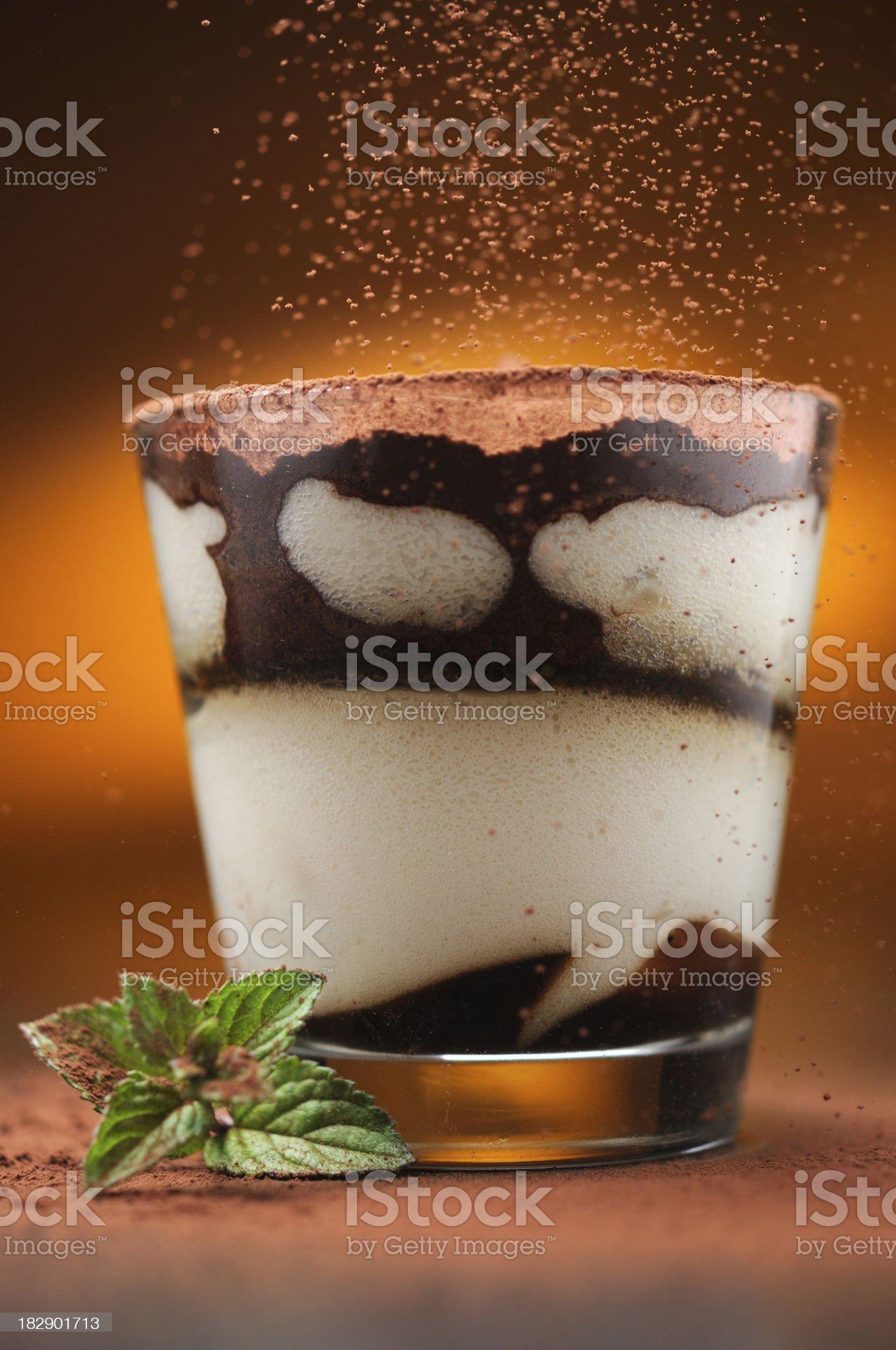 Pouring cacao powder to tiramisu in glass royalty-free stock photo
