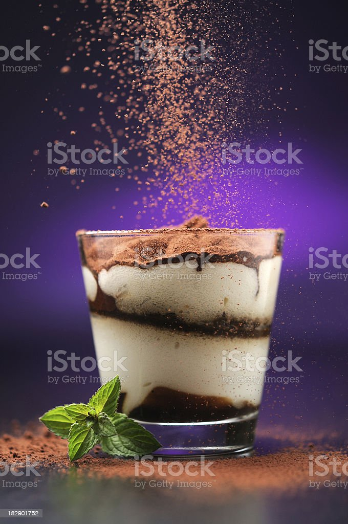 Pouring cacao powder to tiramisu in glass royalty-free stock photo
