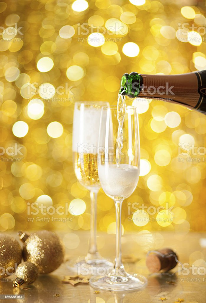 Pouring Champagne in flute with a festive background. royalty-free stock photo