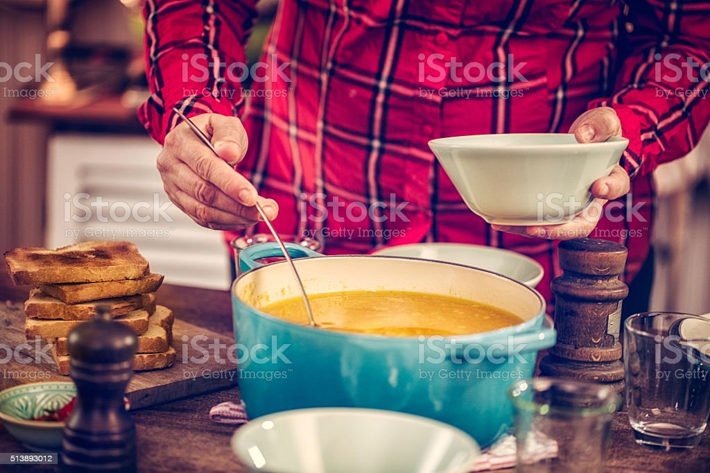 Pouring Chicken Soup with Ladle into a Bowl stock photo