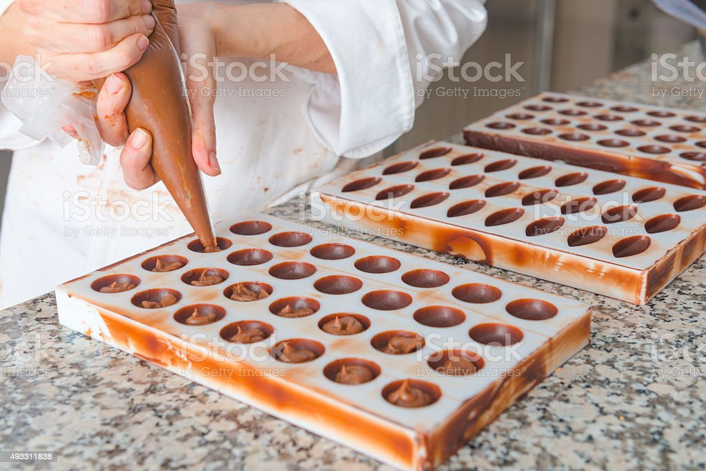 Pouring chocolate into molds stock photo
