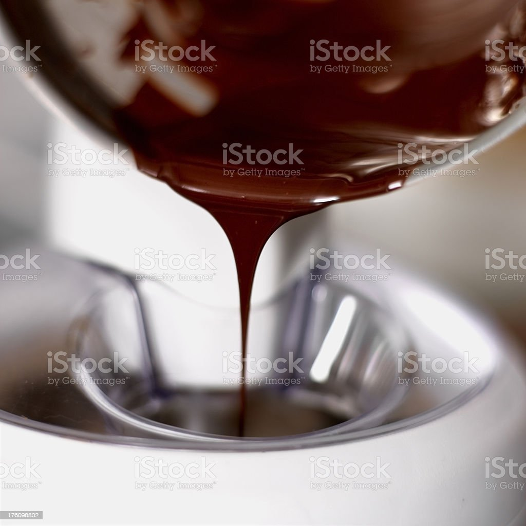Pouring chocolate syrup into ice cream machine stock photo