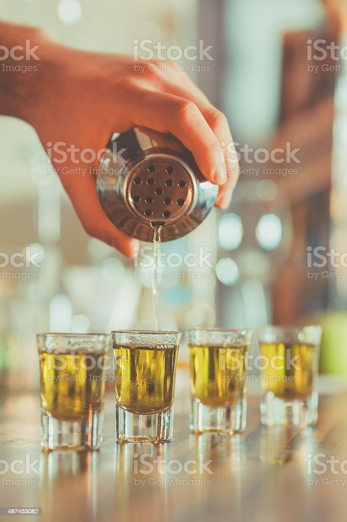 pouring cocktail in shot glasses stock photo