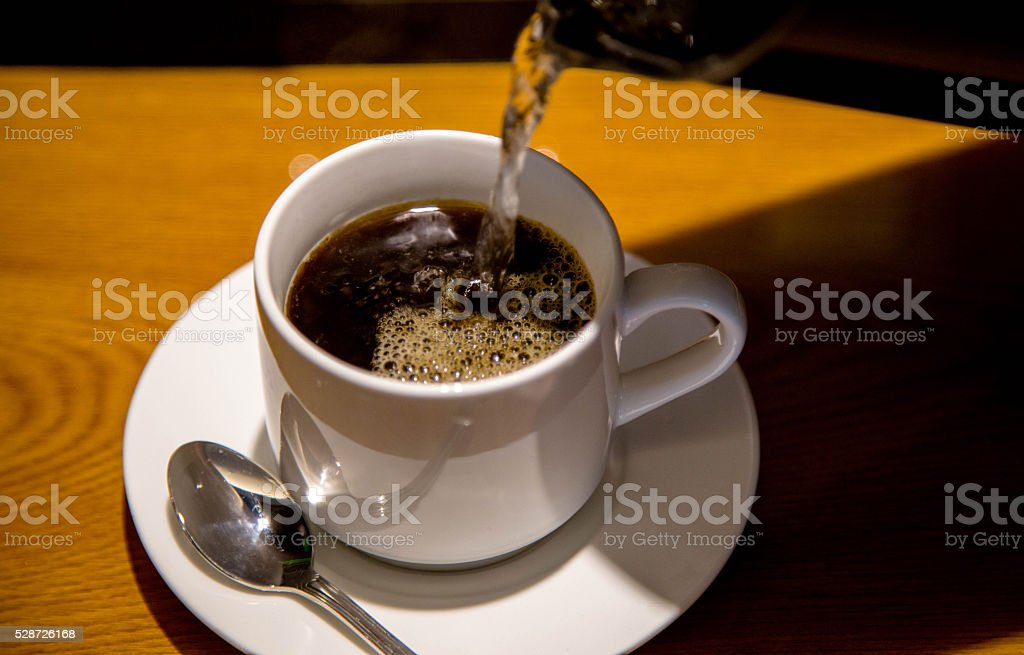 pouring coffee into cup stock photo