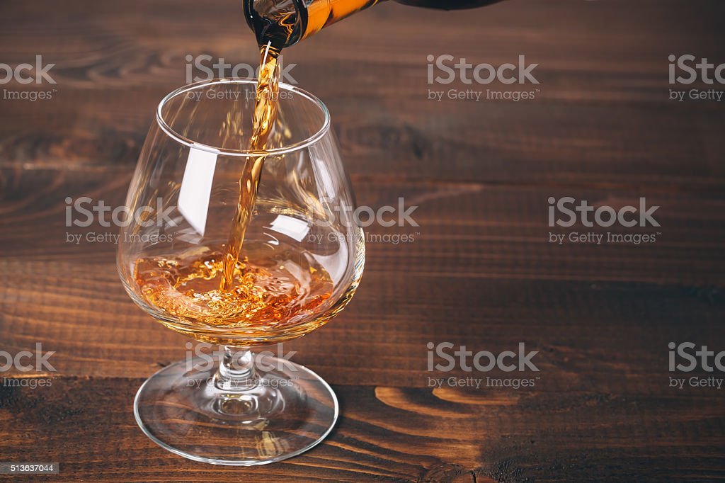 Pouring cognac or whiskey from the bottle stock photo